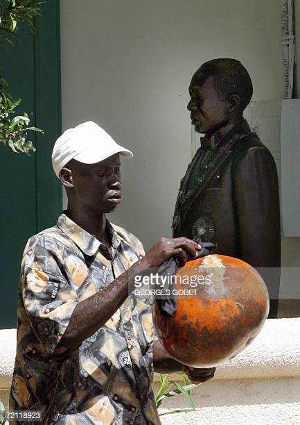Joal-Fadiouth, SENEGAL: Jacques Sarr, conservator of the birth house of Senegalese poet Leopold Sedar Senghor, appears 08 October 2006 near a statue...