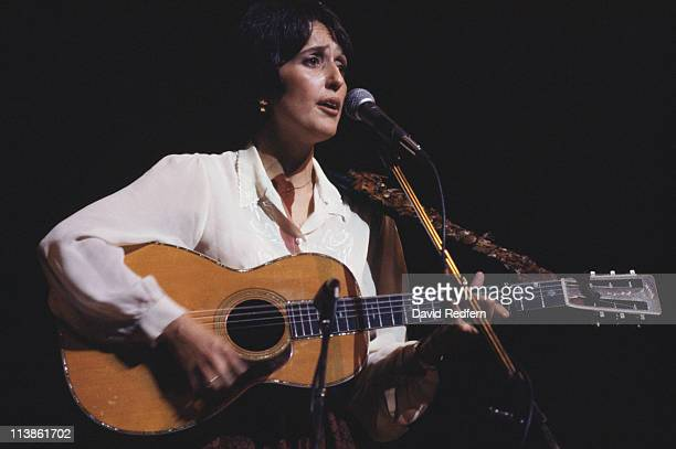 Joan Baez, U.S. Folk singer, playing the guitar and singing into a microphone during a live concert performance at the Hammersmith Odeon in London,...