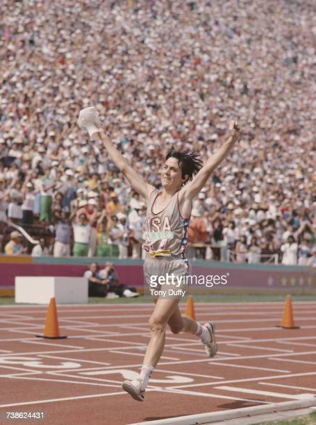 Joan Benoit of the United States raises her arms in celebration after winning the first ever Olympic Women's marathon event at the XXIII Olympic...