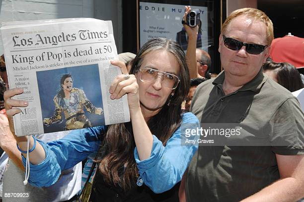 Joan Bryant of Hollywood California holds a copy of the Los Angeles Times with Michael Jackson on the cover as she waits in line with fans at the...