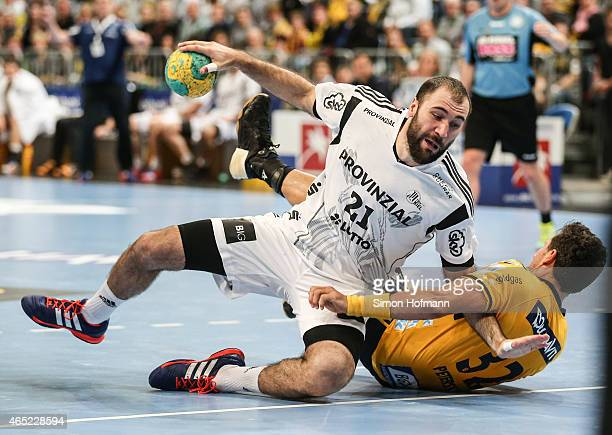 Joan Canellas of Kiel is challenged by Alexander Petersson of RheinNeckar Loewen during the DHB cup quarter final match between RheinNeckar Loewen...