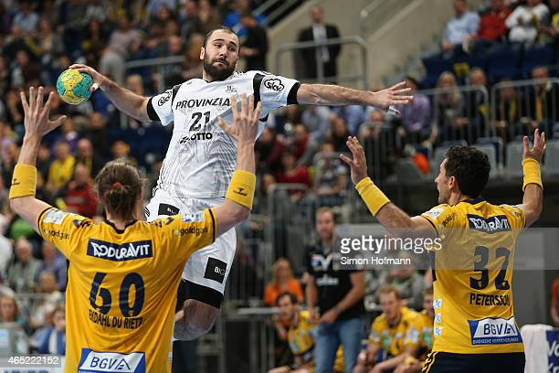 Joan Canellas of Kiel tries to score against Kim Ekdahl Du Rietz and Alexander Petersson of RheinNeckar Loewen during the DHB cup quarter final match...