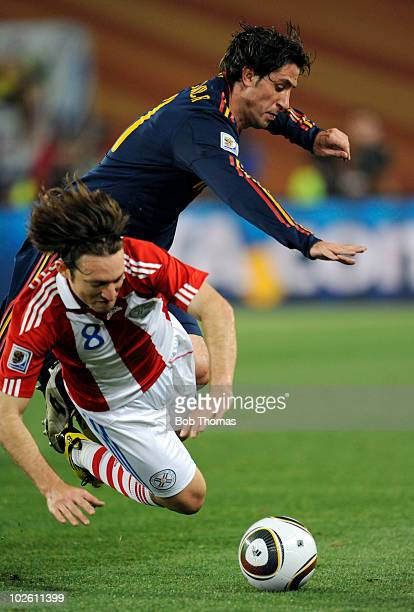 Joan Capdevila of Spain challenges Edgar Barreto of Paraguay during the 2010 FIFA World Cup South Africa Quarter Final match between Paraguay and...