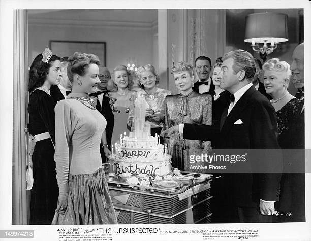 Joan Caulfield smiles as Claude Rains points at birthday cake Constance Bennett and others on the side watching in a scene from the film 'The...