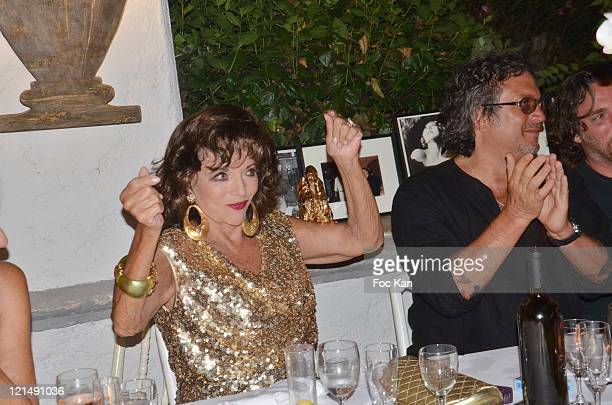Joan Collins and a guest attend the Massimo Gargia Summer Party at Les Moulins de Ramatuelle on August 18, 2011 in Saint Tropez, France.