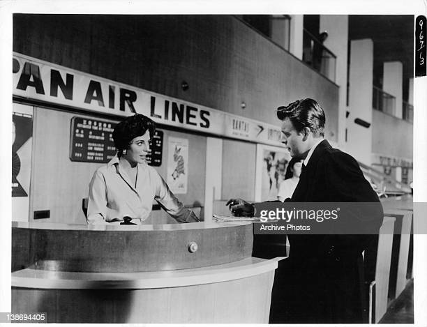 Joan Collins and Robert Wagner at airline ticket counter in a scene from the film 'Stopover Tokyo' 1960