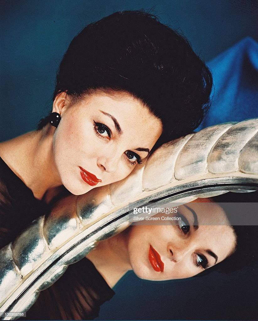 Joan Collins, British actress, posing beside a mirror relects an image of her face, in a studio portrait, against a blue background, circa 1955.
