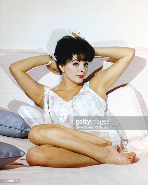 Joan Collins British actress reclining on a white sofa wearing a white dress with her arms behind her head in a studio portrait against a white...