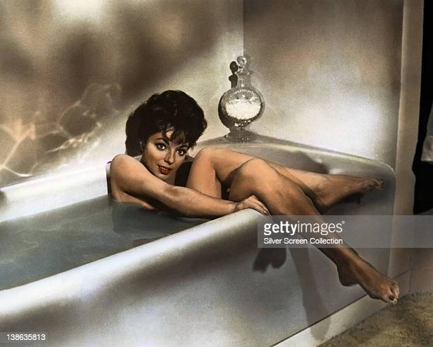 Joan Collins British actress sitting in a bath with her legs hanging over the edge of the bath circa 1955