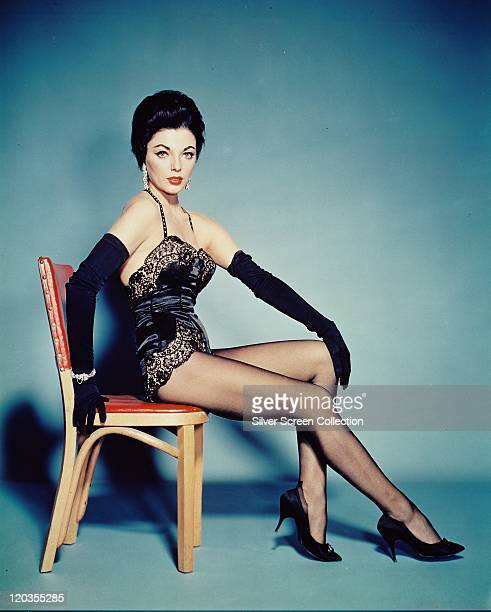 Joan Collins British actress wearing a black silk bustier with black lace trim and long black gloves sitting in a chair in a studio portrait against...
