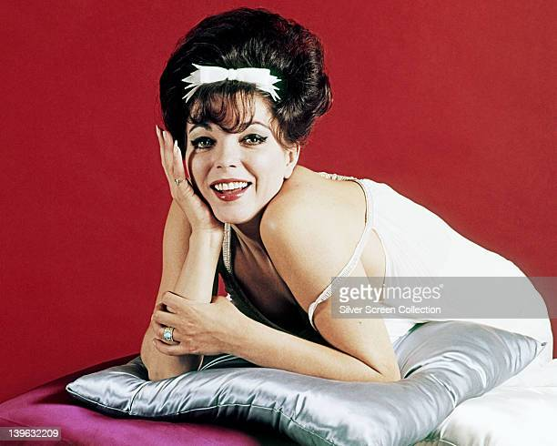 Joan Collins British actress with her hair in a beehive hairstyle with a white bow and wearing a white thin strap top with the left strap falling...