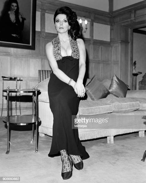 Joan Collins in the Park Street flat she has rented wearing her favourite evening dress of black crepe with a halter bodice with brilliantly coloured...