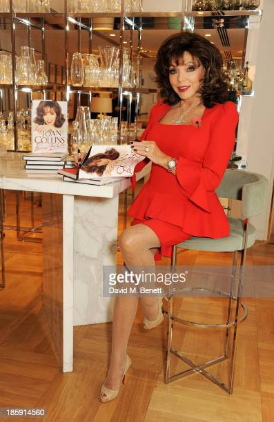 Joan Collins poses with a copy of her book 'Passion For Life' before a fan signing at Selfridges on October 26 2013 in London England