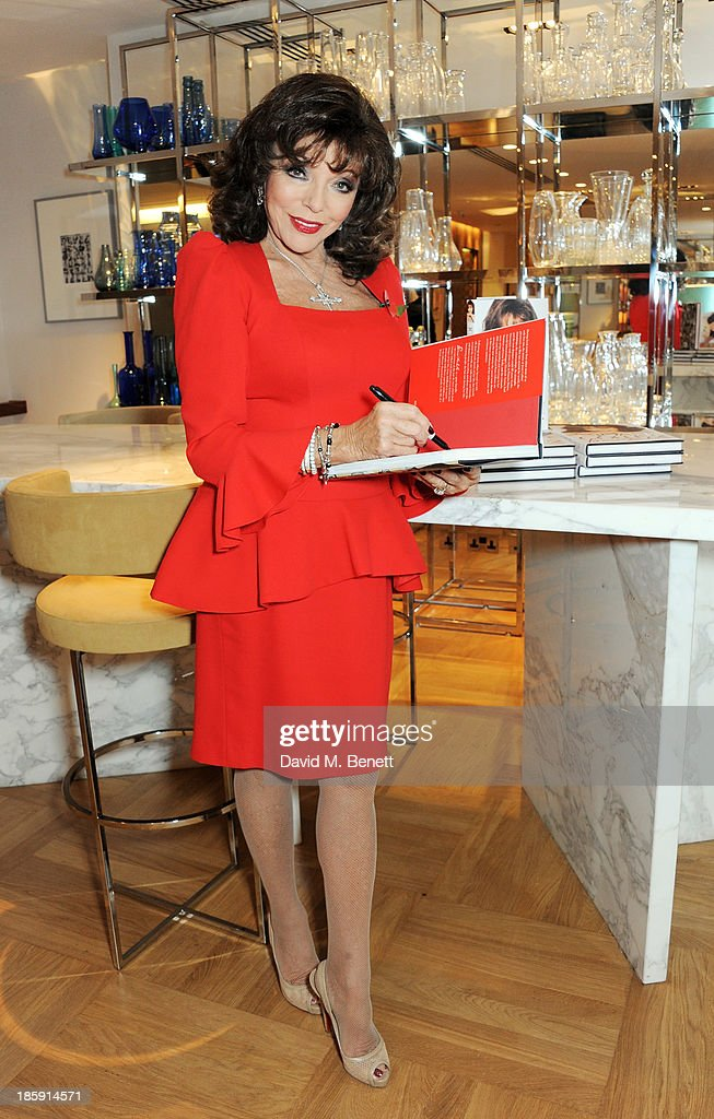 Joan Collins poses with a copy of her book 'Passion For Life' before a fan signing at Selfridges on October 26, 2013 in London, England.