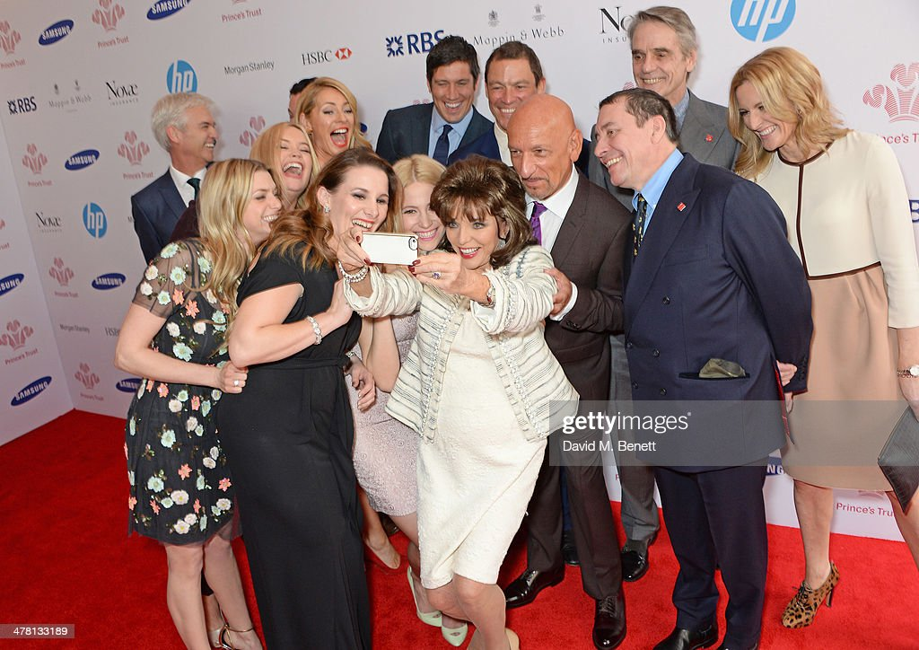 Joan Collins (C) takes a selfie with fellow guests including Phillip Schofield, Anna Williamson, Laura Whitmore, Tess Daly, Sam Bailey, Pixie Lott, Vernon Kay, Dominic West, Sir Ben Kingsley, Jools Holland, Jeremy Irons and Gabby Logan at The Prince's Trust & Samsung Celebrate Success Awards at Odeon Leicester Square on March 12, 2014 in London, England.