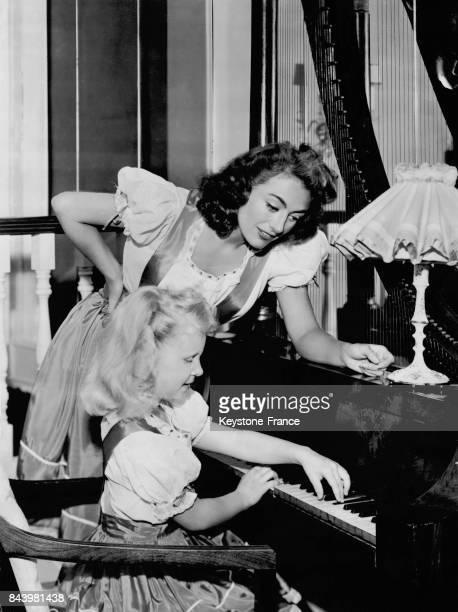 Joan Crawford aidant sa fille Christina lors de sa leçon de piano aux EtatsUnis le 25 juillet 1947