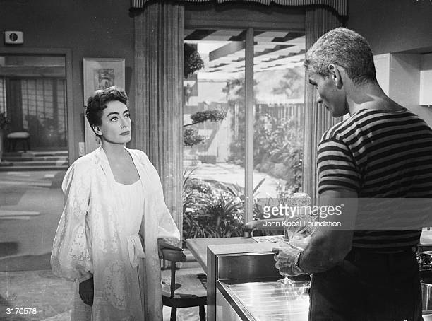 Joan Crawford and Jeff Chandler play a wealthy widow and a handsome gigolo in 'Female on the Beach', a steamy thriller directed by Joseph Pevney.