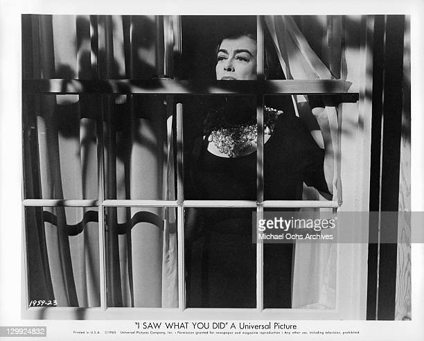 Joan Crawford looking out her window in a scene from the film 'I Saw What You Did' 1965