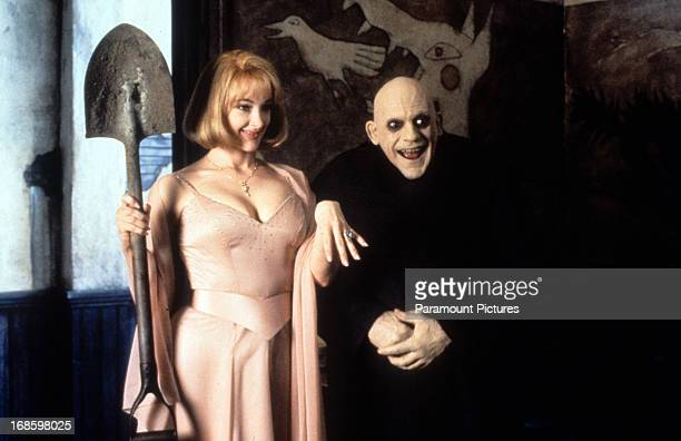 Joan Cusack holding shovel next to a smiling Christopher Lloyd in a scene from the film 'Addams Family Values' 1993