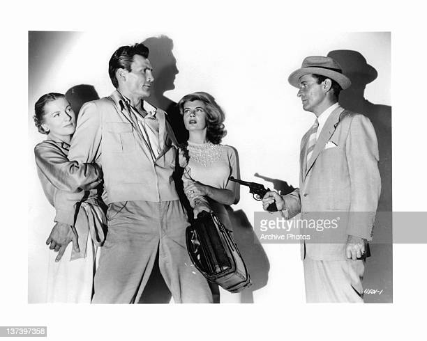 Joan Fontaine and Corinne Calvet hold onto Jack Palance as Robert Douglas points gun at him in a scene from the film 'Flight To Tangier' 1953