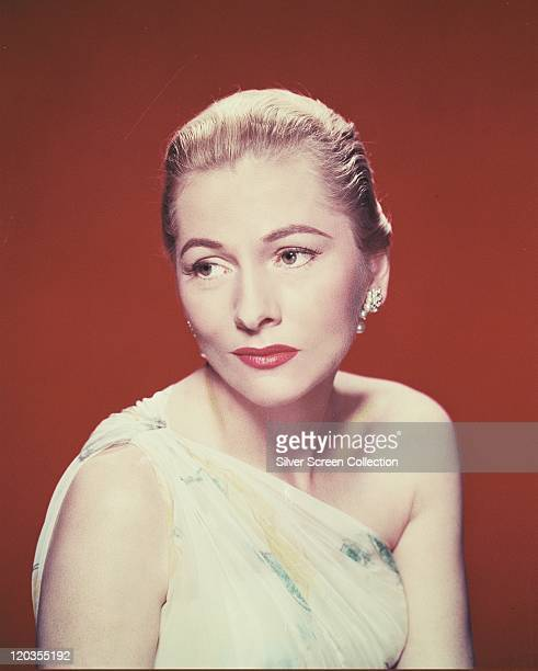 Joan Fontaine British actress wearing a white assymetric top in a studio portrait against a red background circa 1940
