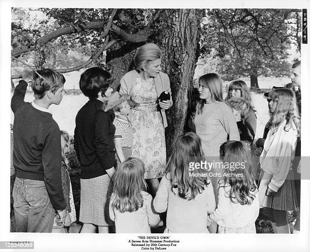 Joan Fontaine looking down at Ingrid Brett in front of a group of people in a scene from the film 'The Devil's Own' 1966