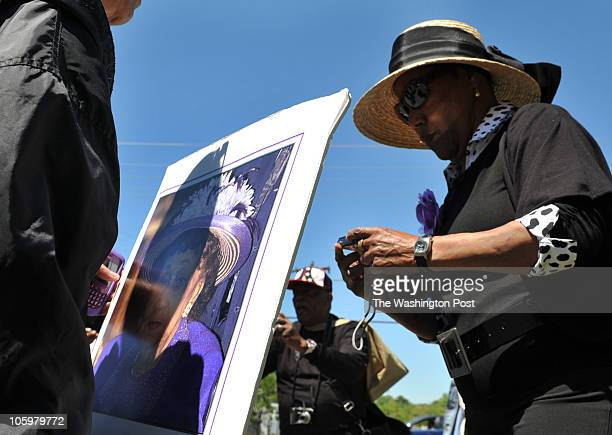 M Joan Johnson prepares to have her photo taken with a photo of civil rights pioneer Dorothy Height outside the gates of Ft Lincoln Cemetery where...