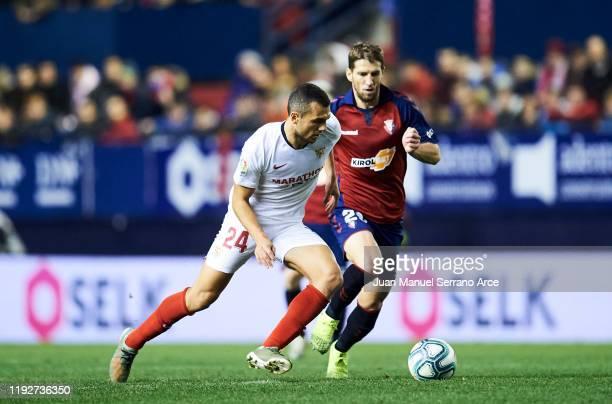 Joan Jordan of Sevilla FC duels for the ball with Darko Brasanac of CA Osasuna during the Liga match between CA Osasuna and Sevilla FC at El Sadar...