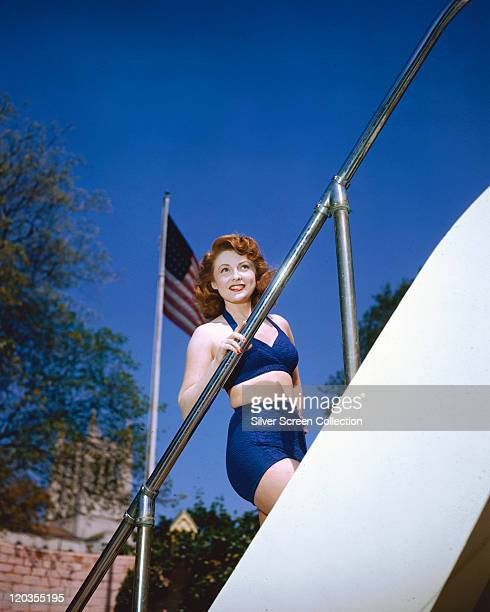 Joan Leslie US actress wearing a blue swimsuit while holding onto a bannister of a starcase with a starsandstripes flag flying in the background of...