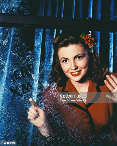 Joan Leslie US actress wearing a red jacket with black trim with red berries in her hair in a studio portrait circa 1955