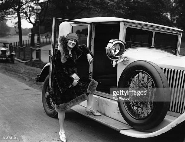 Joan Lockton stands on the running board of her Renault in Hyde Park as she takes part in the mannequin parade