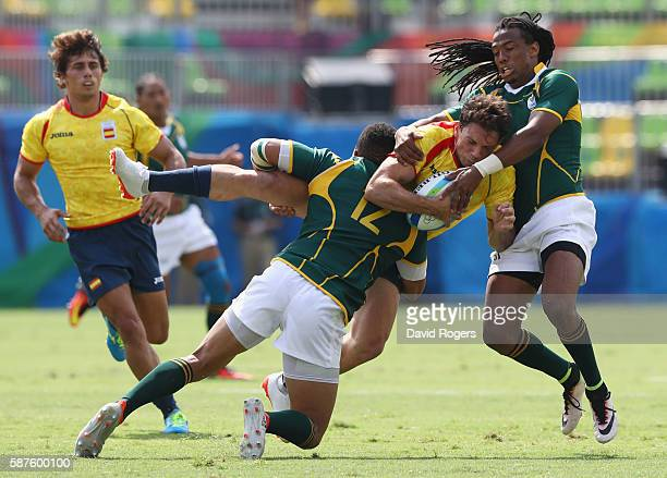 Joan Losada of Spain is tackled by Juan de Jongh and Cecil Afrika of South Africa during the Men's Rugby Sevens Pool B match between South Africa and...