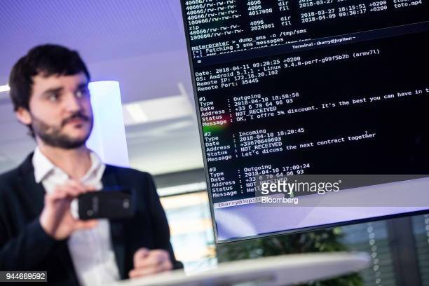 Joan Mazenc an ethical hacker stands beside a screen of Short Message Service text during a demonstration at the Thales SA cyber security event in...