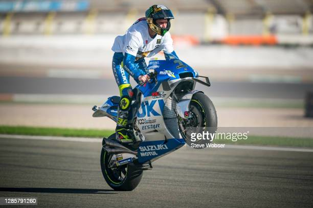 Joan Mir of Spain and Team SUZUKI ECSTAR rides a wheelie with his special title helmet and shirt after winning his first MotoGP title during the...