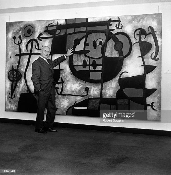 Joan Miro with one of his paintings at his one man exhibition at the Marlborough Fine Art Galleries