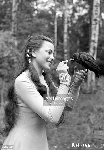 Joan Rice , the British leading lady and former waitress, holds a tame bird on her finger while she feeds it in a scene from 'The Story Of Robin Hood...