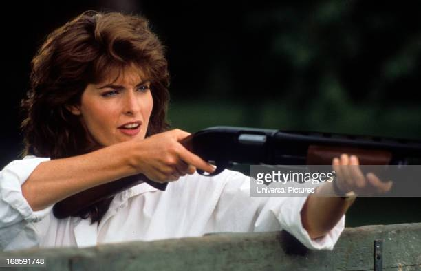 Joan Severance pointing a rifle in a scene from the film 'Bird On A Wire' 1990
