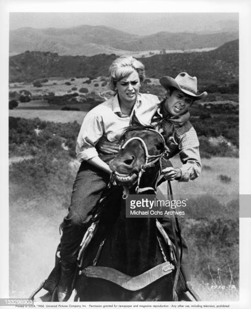 Joan Staley is helped onto the horse of Audie Murphy when hers bolts away in a scene from the film 'Gunpoint' 1966