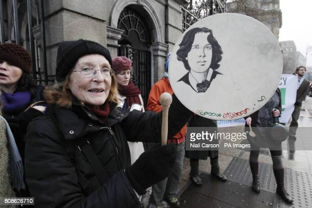 Joan Swift bangs a bodhran decorated with picture of Oscar Wilde as she joins a group set up on facebook banging pots and pans outside Leinster House...