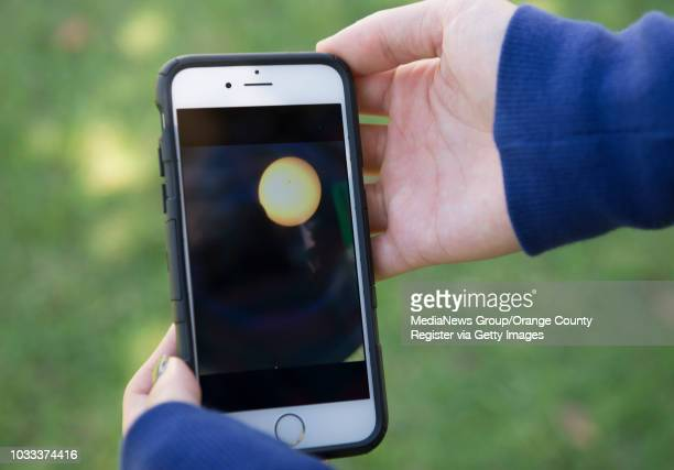 Joann Chang a junior at Cal State Fullerton shows the cell phone photo she took of the partial solar eclipse through the viewfinder a the telescope...