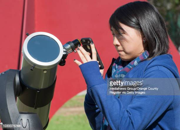 Joann Chang a junior at Cal State Fullerton takes a cell phone photo of the partial solar eclipse through the viewfinder of the telescope setup...