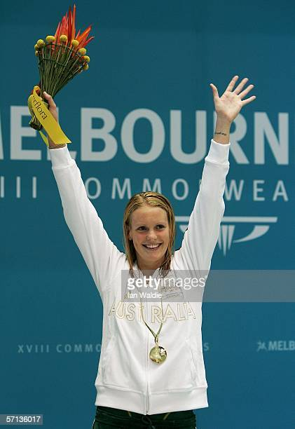 Joanna Fargus of Australia waves to the crowd wearing her gold medal after winning the women's 50m freestyle final at the swimming held at the...