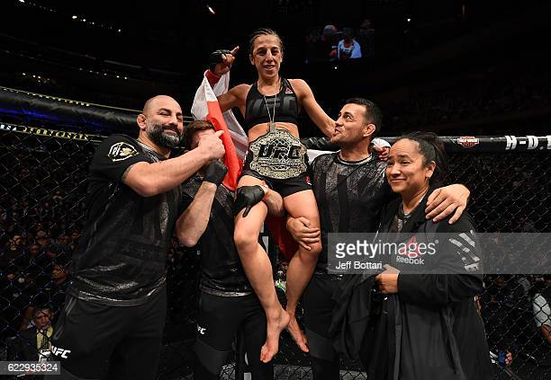 Joanna Jedrzejczyk of Poland is awarded the belt after her unanimous decision victory in their women's strawweight championship bout against Karolina...