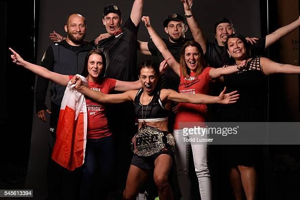 Joanna Jedrzejczyk of Poland poses for a portrait with her family and team after her victory over Claudia Gadelha during The Ultimate Fighter Finale...