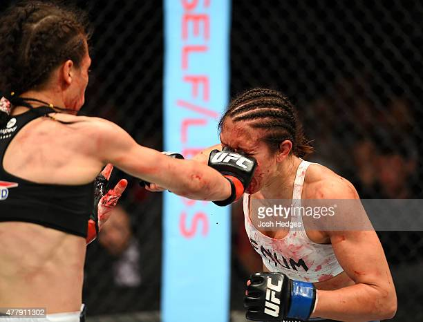 Joanna Jedrzejczyk of Poland punches Jessica Penne of the United States in their women's strawweight championship bout during the UFC Fight Night...