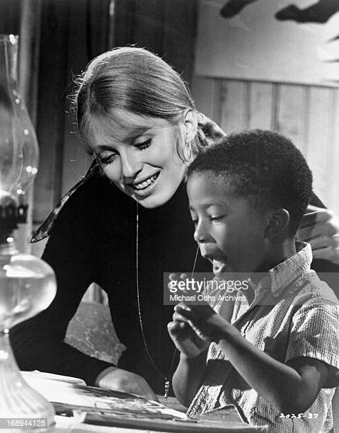 Joanna Shimkus helps a child in a scene from the film 'The Lost Man' 1969