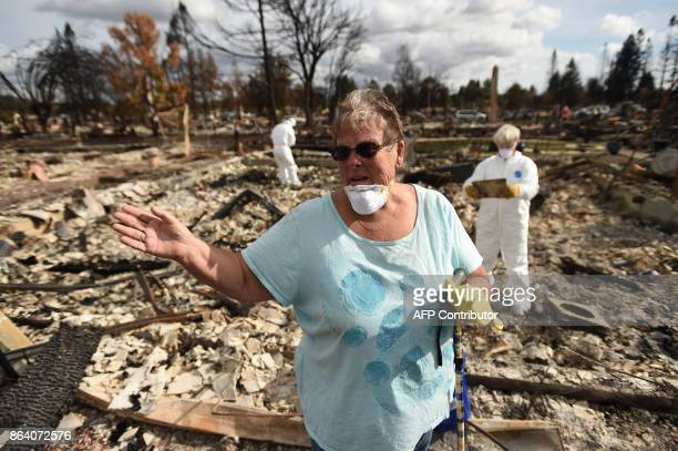 Joanne Bartlett and her neighbours search for remains at her burned residence in the Coffey Park area of Santa Rosa California on October 20 2017...