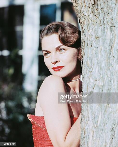 Joanne Dru US actress wearing a red strapless top posing beside a tree trunk circa 1950