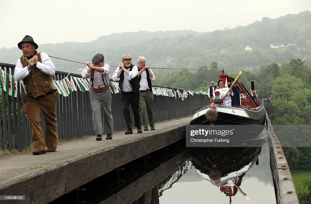 Joanne Gregory carries the Olympic Torch on a hand drawn canal boat across the Pontcysyllte Aqueduct, a UNESCO World Heritage Site on May 30, 2012 in Llangollen, Wales. The Olympic Flame is now on day 12 of a 70-day relay involving 8,000 torchbearers covering 8,000 miles.