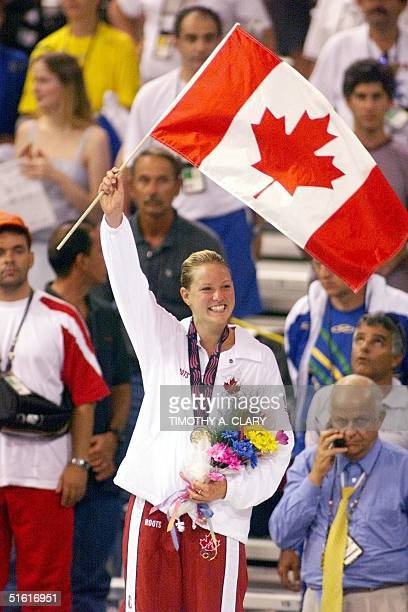 Joanne Malar of Canada raises the Canadian flag after receiving her gold medal for winning the women's 200m medley 06 August 1999 at the XIII Pan...